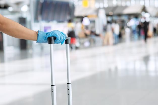 空港ターミナルでハンドルの荷物を保持しているニトリル手袋を身に着けている若い女性旅行者、保護コロナウイルス病(covid-19)感染。新しいノーマルとトラベルバブルのコンセプト