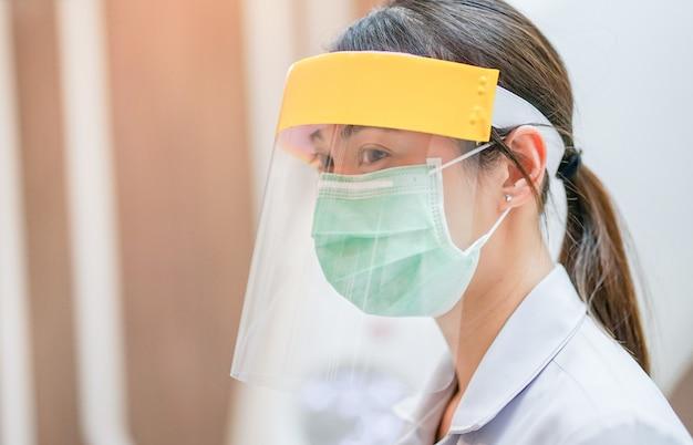 病院でコロナウイルスcovid-19ウイルスを保護するためにフェイスシールドと医療マスクを身に着けている医療スタッフ