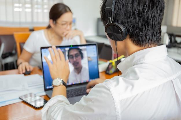 自宅からのラップトップ作業を使用したビジネスマンのビデオ会議はcovid-19を防ぎます。