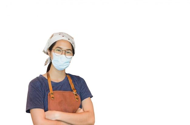 Covid-19防止中にカフェに立っている防護マスクを身に着けているアジアの女性。