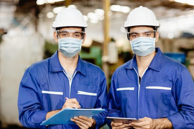 業界の男性労働者は、covid-19ウイルスの空気塵の汚染を防ぎ、健康のために、工場での作業中にフェイスマスクを着用します。