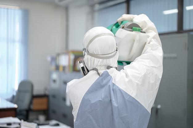 Covid-19を防ぐオフィスの消毒、オフィス、コロナウイルスのコンセプトで消毒した白い防護服の人