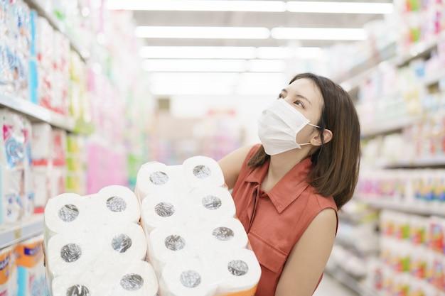 Распространение covid-19. женщина в медицинской защитной маске паники покупки салфеткой. страх коронавируса.