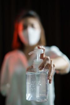 手を洗うためのアルコールジェル、コロナウイルスまたはcovid-19保護を共有する女性。
