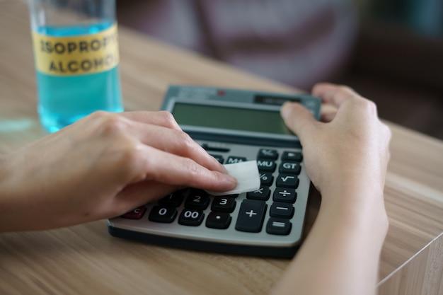 コロナウイルスまたはcovid-19保護用のイソプロピルアルコールを使用した女性用のきれいな計算機。