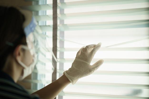 窓のブラインドを通して見る保護医療スクリーンまたはプラスチック製の顔面シールドを身に着けている女性。コロナウイルスまたはcovid-19保護用