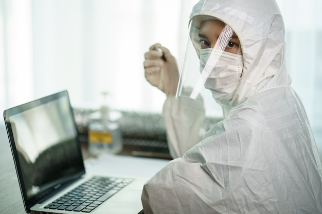 研究室で分析する研究室コンピューターで防護化学防護服の労働者の女性。コロナウイルスやcovid-19の拡散を止める。