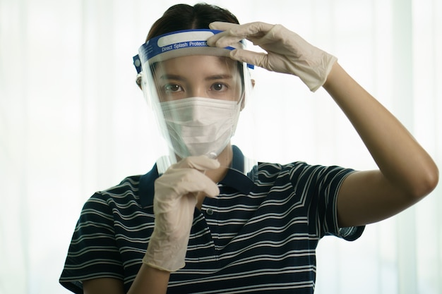 コロナウイルスまたはcovid-19保護のために、保護用の医療用スクリーンまたはプラスチック製のシールドを顔に装着している女性。