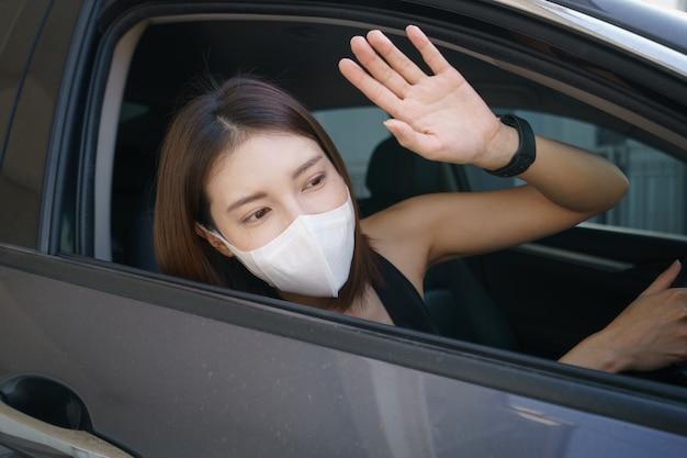 コロナウイルスまたはcovid-19保護のために、車の中でサージカルマスクを身につけている女性。