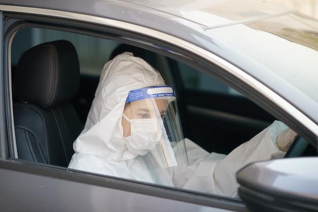 手袋、防護服、顔面シールド、マスクの女性ドライバー。コロナウイルスまたはcovid-19保護。