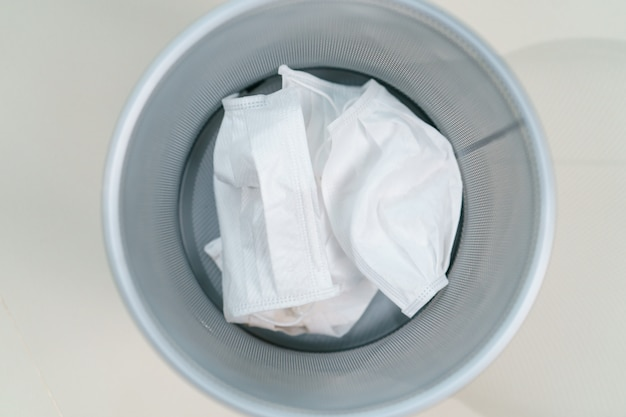 医療用ごみ箱で使用されているフェイスマスク。コロナウイルス、covid-19の蔓延防止。