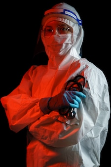 コロナウイルスまたはcovid-19保護用の防護服を着ている女性医師。防護服、顔面シールド、手袋、マスク、聴診器。