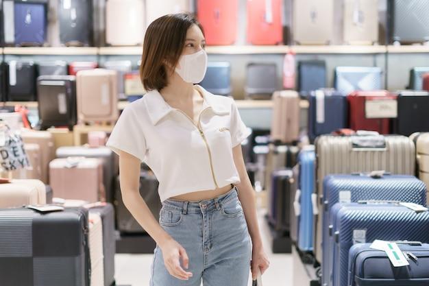 Женщина в маске выбирает багаж в магазине во время эпидемии covid-19. подготовка к путешествию после коронавирусного кризиса.