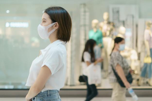 コロナウイルス予防のためのショッピングモールcovid-19を歩きながらフェイスマスクを着ている女性。
