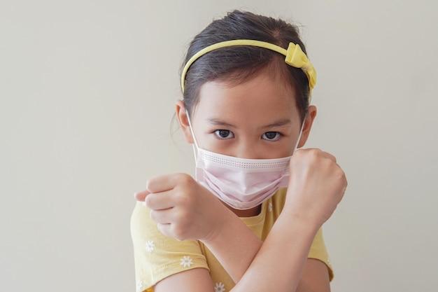 アジアの少女医療フェイスマスクを着用し、一時停止の標識、自己検疫、コロナウイルス、covid-19ウイルスの発生流行のパンデミックを作ります。
