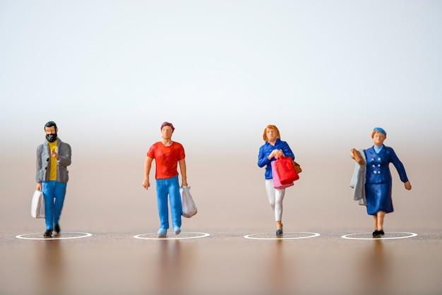 買い物客のミニチュアの人々は、covid-19コロナウイルスの蔓延とパンデミック感染を防ぐために、ショッピングモールと公共エリアで距離を保ちます。社会的距離の概念。