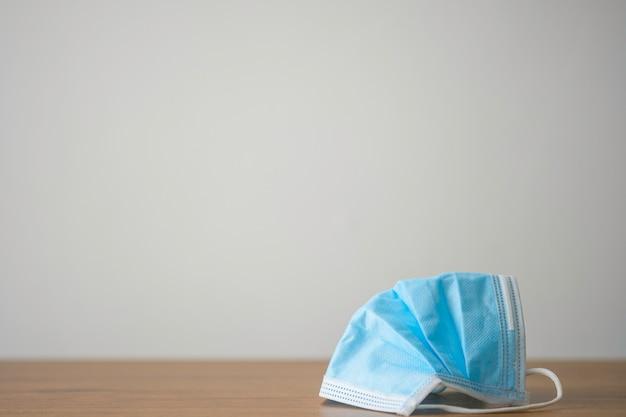 Covid-19またはコロナウイルス、汚染のほこり、バクテリアから身を守るために着用する木製のテーブルの青い外科用フェイスマスク。ヘルスケアと外科の概念。