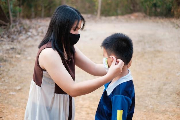 母親は息子をcovid-19ウイルスから保護するためにマスクを着用しています。