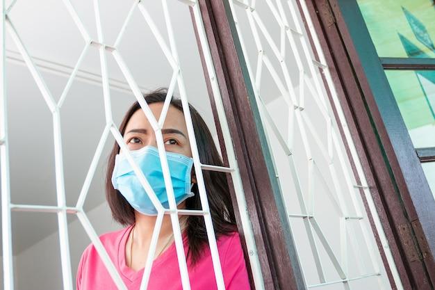 コロナウイルスcovid-19、自宅での拘留中マスクされた女性家で一人で悲しくて孤独な感じ時々彼女は彼女の電話を使って友達にビデオ通話をします