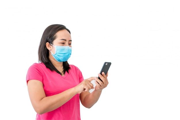 コロナウイルスcovid-19、自宅での拘留中マスクされた女性は電話を使って友達にビデオ通話をします。