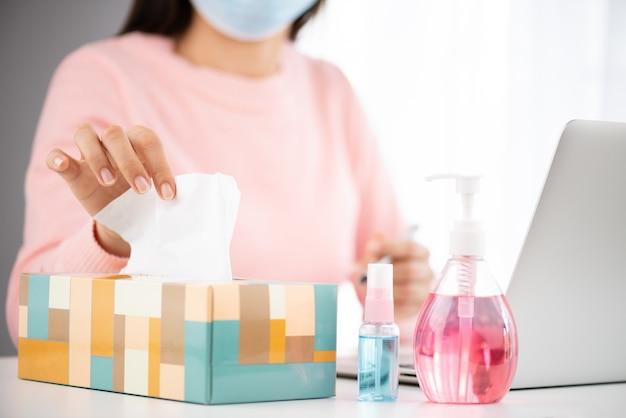 病気の女性がコロナウイルス(covid-19)の予防のために咳をしながら白いティッシュペーパーを服用している。