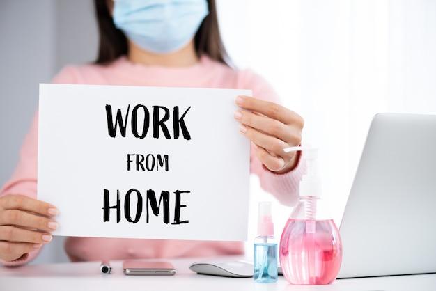 Женщина держит белую с работы из домашнего текста для предотвращения коронавируса (covid-19).
