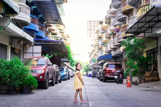 夕暮れとcovid-19屋外に対してマスクを身に着けている小さなアジアの女の子