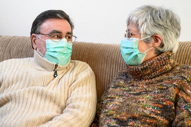Covid-19、家のライフスタイルを保ちます。陽気な高齢者のカップルが保護マスクを付けてソファーに座って笑いながらお互いを見つめ、自宅での検疫中にポジティブである。