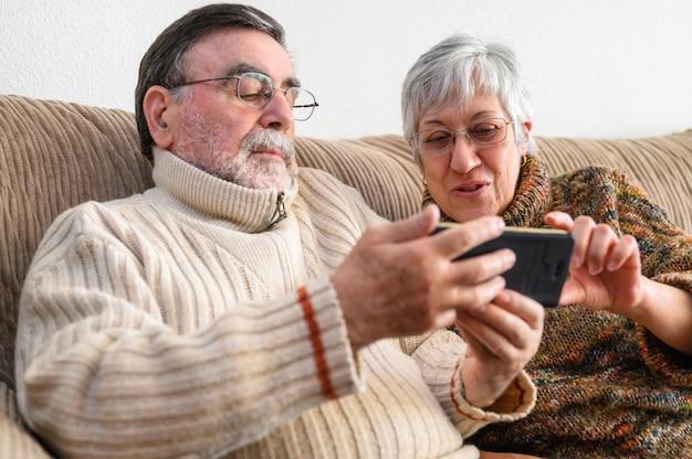 Covid-19は家にいます。幸せな引退した年配のカップル、携帯電話で家族のビデオ通話を行います。社会的距離、肯定的な表現。