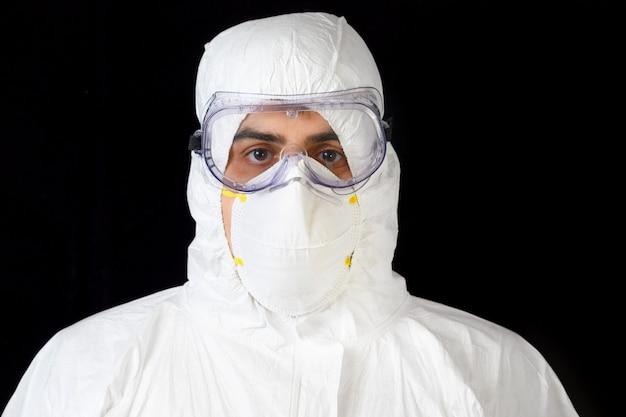 Covid-19保護具。分離された黒の個人用保護具を身に着けている医師または男性看護師の肖像画