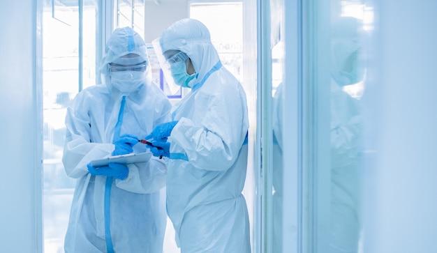 コロナウイルスをスクリーニングするための血液サンプルのテストチューブを保持している検疫患者チャートにマスクを書き込んでいる個人用保護スーツのアジア女性医師。コロナウイルス、covid-19コンセプト。