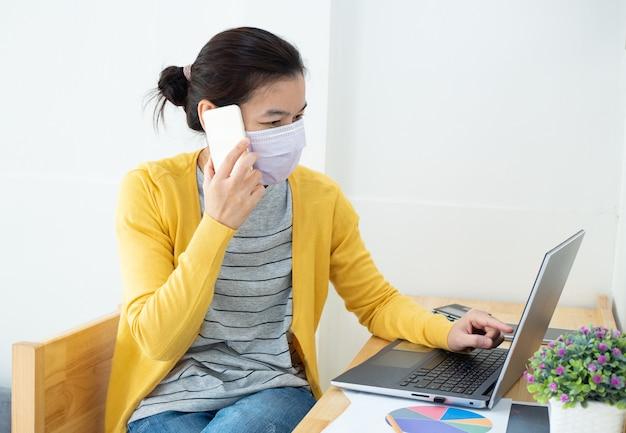Азиатские женщины в масках работают дома или работают удаленно, используя смартфон, чтобы уменьшить распространение коронавирусной инфекции во время вспышки covid-19.