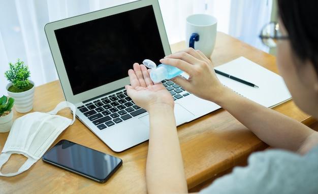 アジアの女性はノートブックを使用して自宅で仕事をし、ボトルからアルコールジェルを使用して手をきれいにし、covid-19の危機中のコロナウイルスの拡散を防ぎます。