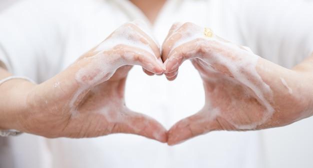 アジアの女性は石鹸で手を洗ったりきれいにしたりして、手札を作り、covid-19の発生中に励ましを送ります。