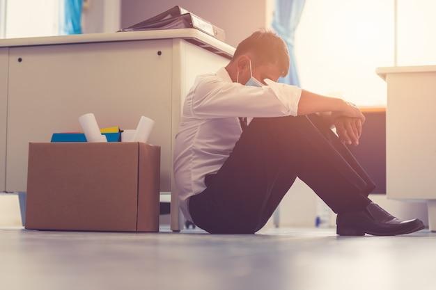 Covid-19の世界的な影響によるビジネスの失敗と失業問題の概念を却下された後、悲しいアジアのビジネスマンが部屋の外に座って解雇しました。