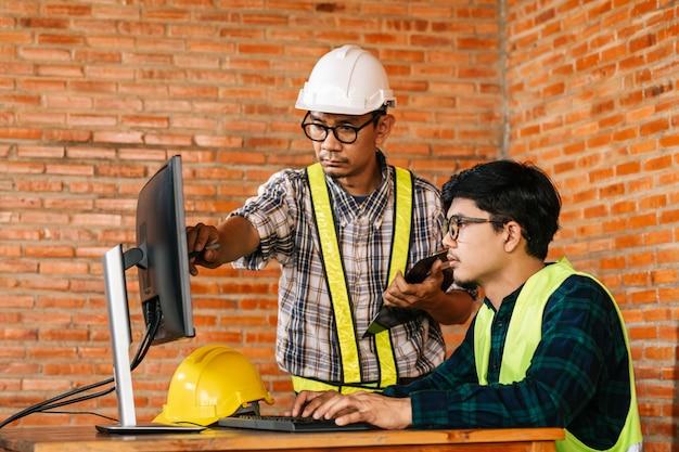 Covid-19と社会的距離の世界的な影響による、レビューのためにモニターを介して建設現場で働くエンジニアとアーキテクトの建設コンセプト。