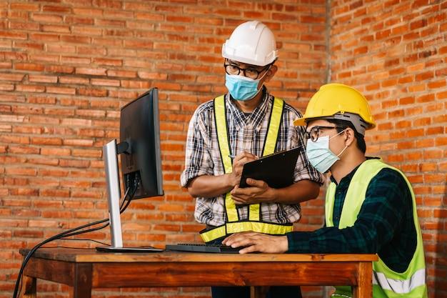 エンジニアとアーキテクトの建設コンセプトは、covid-19と社会的距離の世界的な影響のため、レビューのために建設現場のモニターを介して働く医療用マスクを着用することです。