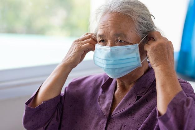 Лицевая маска старшей азиатской женщины нося во время вспышки вируса и гриппа короны. защита от болезней и болезней. стареющая пациентка, подверженная риску заражения коронным вирусом [covid-19].