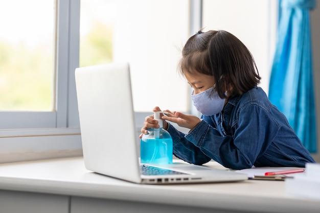 コロナウイルス[covid-19]が家にいるのを防ぐために、アジアの若い女の子がアルコールジェルで手を洗っています。
