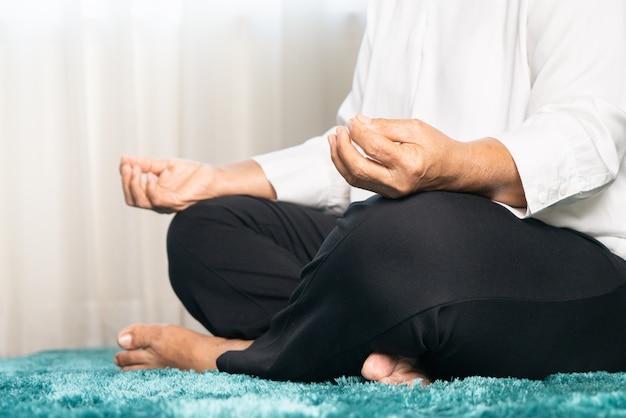 Covid-19 карантинная активность для пожилой женщины, медитирующей оставаться дома, чтобы избежать риска