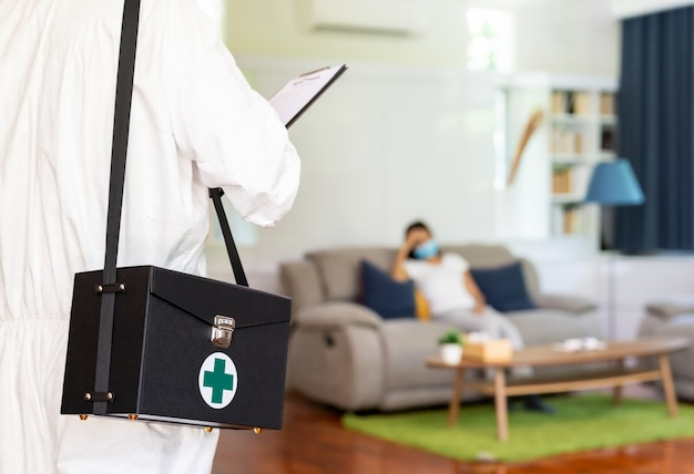 Закройте вверх по медицинскому персоналу в личном защитном костюме сиз на фоне азиатской женщины с лицевой маской, ожидающей в гостиной квартиры. концепция доставки коронавируса covid-19 дома.