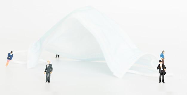 Миниатюрные бизнесмены проводят дистанционное дистанцирование с помощью хирургической маски на белом фоне, чтобы обезопасить себя от коронавирусной болезни (covid-19).