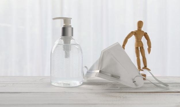 Дезинфицирующее средство для рук, хирургическая маска, деревянная кукла на деревянном столе с мягкой белой предпосылкой пока домашний карантин covid-19.