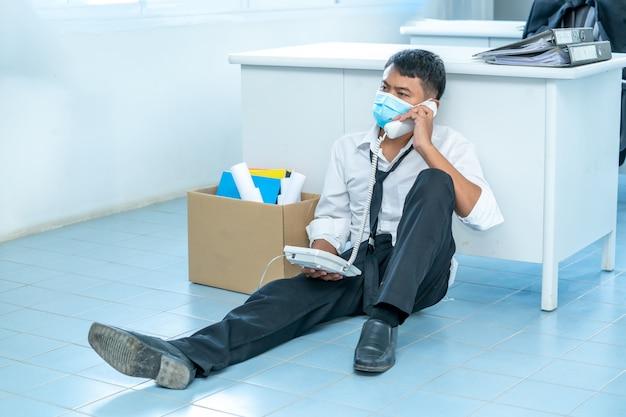 失業者、実業家は茶色の段ボール箱を持ち、covid 19の病気の状況から仕事を辞退する理由を示す辞任書を書いています。コロナウイルスは世界的な緊急事態になりました。