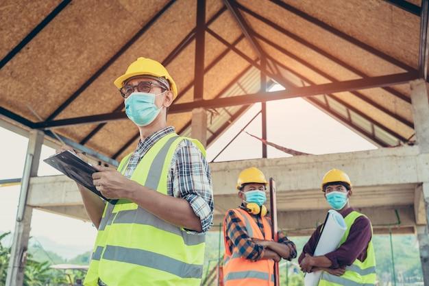 粉塵を防ぐために防護マスクを身に着けている企業の労働者と建設現場の建設現場で働くcovid 19は、コロナウイルスが世界的な緊急事態に変わりました。