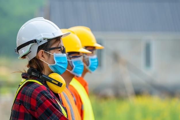 工場でcovid-19から保護するための防護マスクを身に着けている労働者、建設現場の概念における伝染病からの安全管理。
