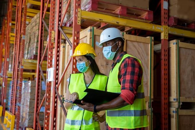 倉庫で働くcovid-19から身を守るために防護マスクをつけている倉庫作業員。