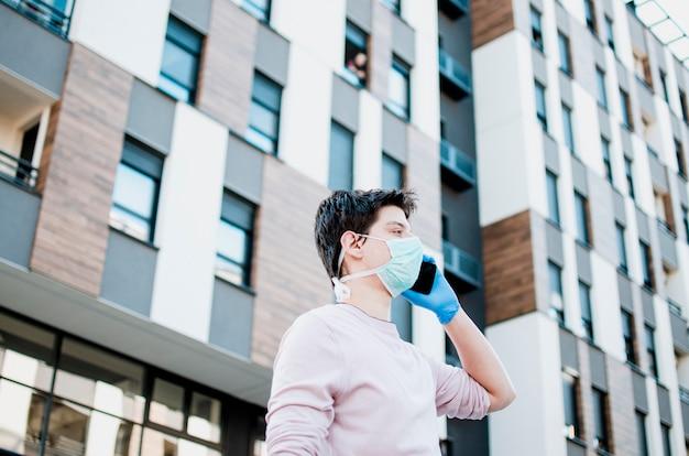 Человек с защитной медицинской одежды с помощью мобильного телефона, ходить по улице города. мужчина в защитной маске и перчатках на улице. ответственное поведение во время пандемии covid-19.