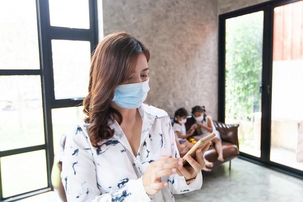 在宅勤務コロナウイルスcovid-19の隔離中の女性スマートフォンで保護マスクを着用し、コロナウイルスの発生中に自宅で遊んでいる子供たちが自宅で作業している