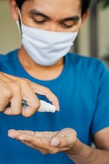 Covid-19を閉じる男はマスクを着用し、自宅のコロナウイルスに対してハンドジェルディスペンサーを洗う。